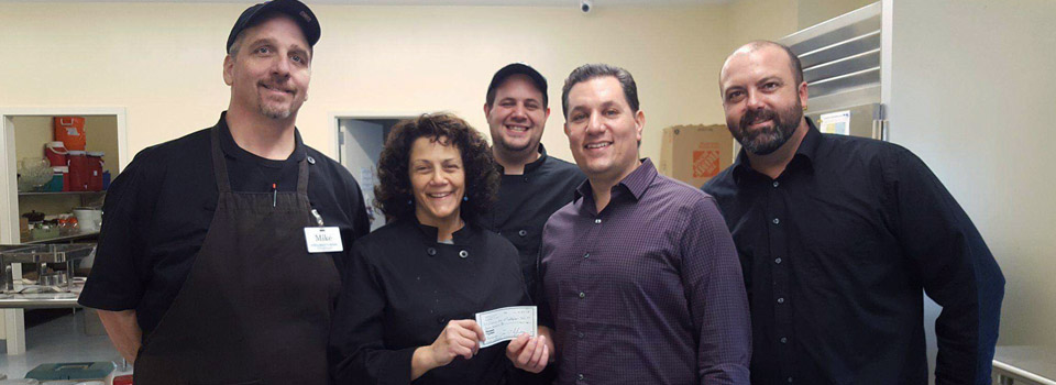 photo of kitchen staff with donation check