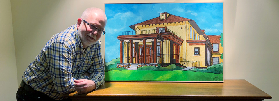 photo of man posing in front of a painting of the old front of the Children's Home